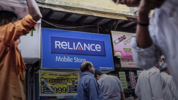 Pedestrians walk past a Reliance Communications Ltd. Mobile Store in Mumbai, India.