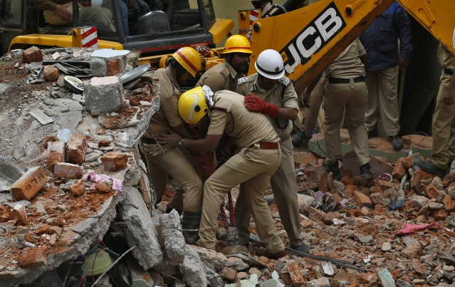 Rescue workers remove the debris to look for survivors at the site of a building that collapsed in Bangalore, India, Monday, Oct. 16, 2017. A two-story building collapsed early Monday when a cooking gas cylinder exploded in a residential building in southern India.