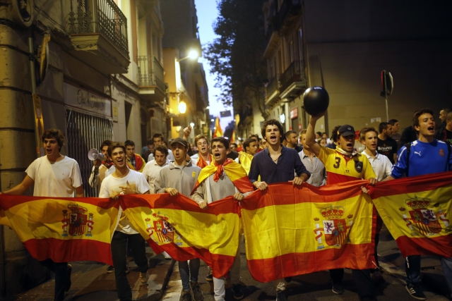 Anti-Catalan independence demonstrators carry a Spanish flag as they march in Barcelona, Spain on Tuesday, 3 October 2017.