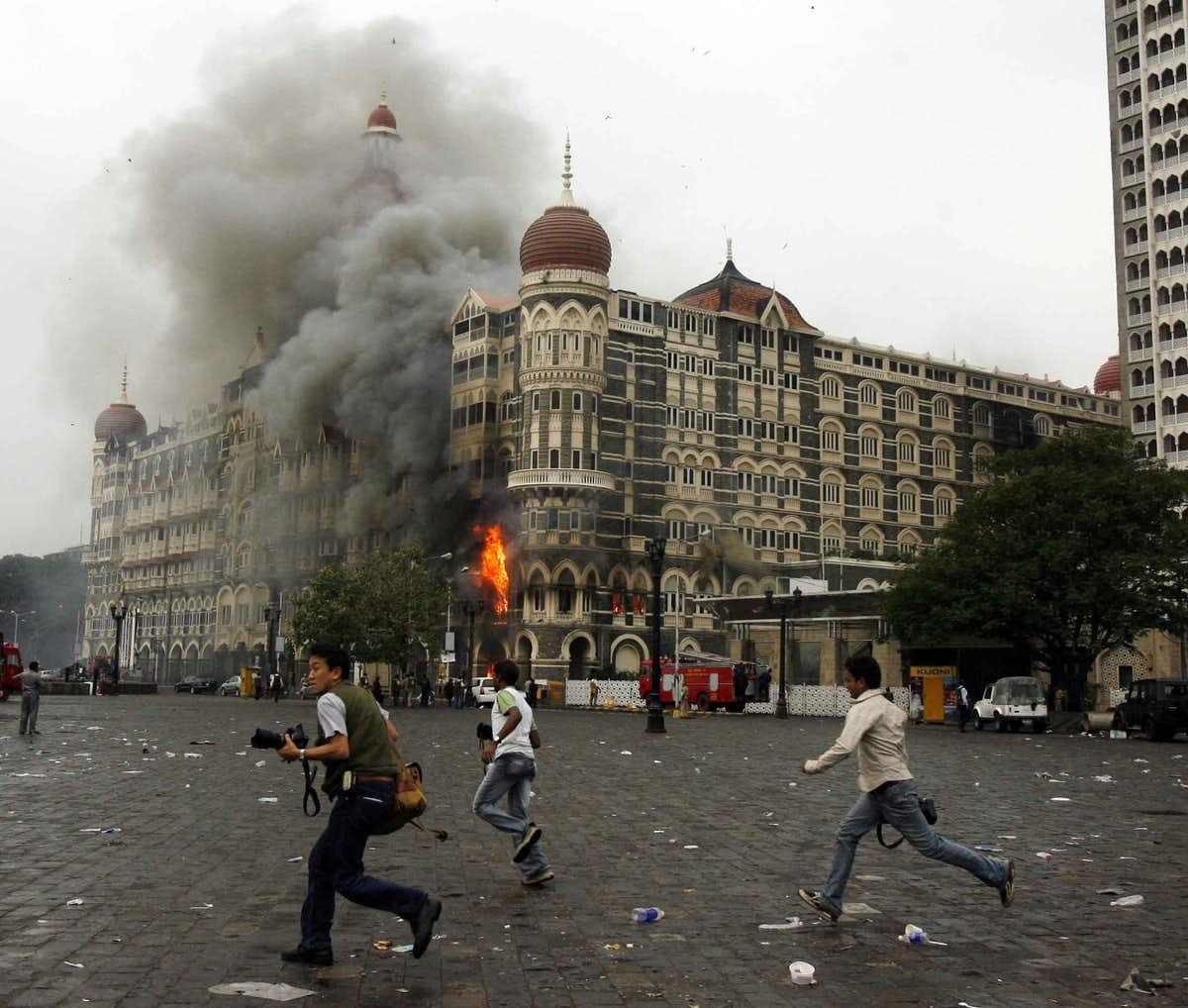 Journalists run for shelter as the Taj Mahal Hotel in Mumbai burns under fire from terrorists cooped inside.