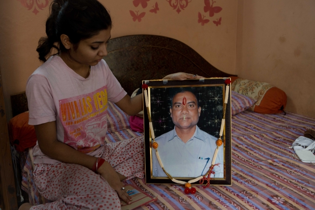 Shruti holds up her father's portrait. She hasn't been able to continue her studies ever since Ravi's death.