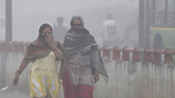 Women cover their face while walking through dense smog in New Delhi on Wednesday.