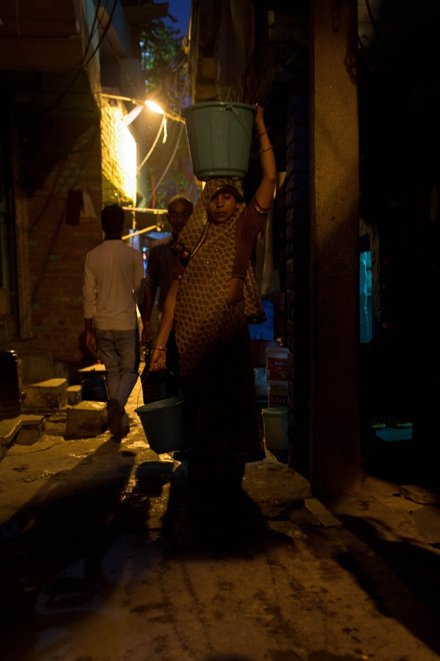 A woman carrying a bucket of water  from a nearby tap in Kabir Nagar basti, north Delhi.