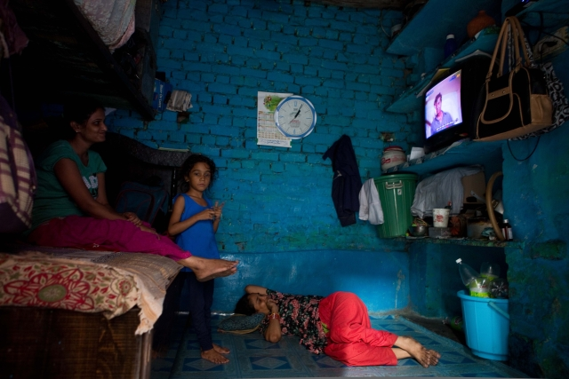 A family watching television inside their one room house in Chandrawal basti, north Delhi.