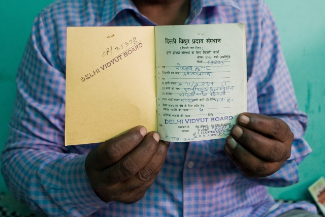 Rohtash Kumar a resident of Chandrawal Basti shows his yellow card.
