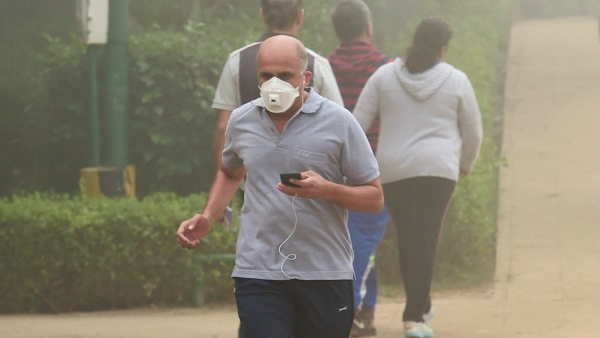 A man, wearing an anti-pollution mask, jogs through smog at Lodhi Garden in New Delhi on Tuesday, 7 November.