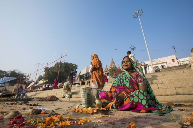A woman awaits as her family takes the holy dip in Varanasi's ghats.