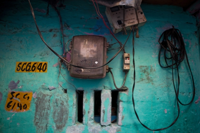 A metre seen in Sanjay Basti, North Delhi. Tata Power-DDL, that provides electricity in the area, have a yellow plate marking as none of the houses in the basti have house numbers.