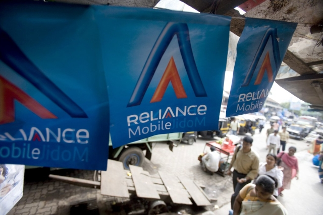 Pedestrians walk past RCom banners near a recharge shop.