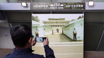 A visitor takes a picture of a picture of JSA, where the soldier was rescued by the South Korean military.