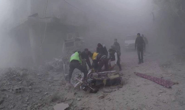 Civil Defense workers carry an injured man after government airstrikes hit Douma, near Damascus, Syria