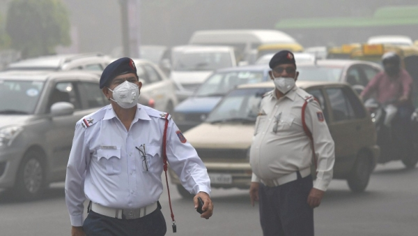 Traffic policemen wear masks to protect themselves from heavy smog and air pollution while manning the traffic in New Delhi.