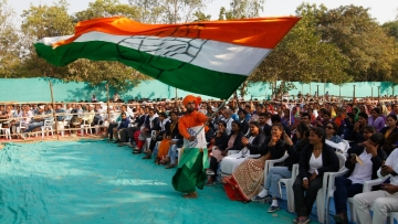 A supporter waves a Congress flag at an election rally in Gujarat.