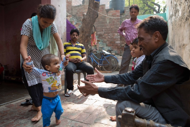 Suresh plays with his one-year-old grandson.