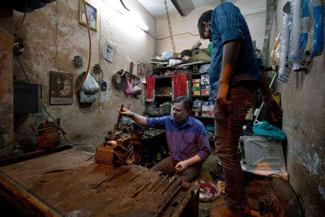 Nand Kishor and his son Vishal at their small electric repair shop in Chandrawal, north Delhi.