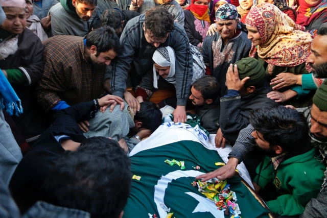 Militant Basit Rasool Dar's brother cries over his body during his funeral procession in Marhama in Kashmir December 2016.