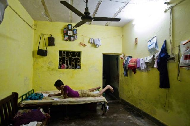 A kid studies under a tube light inside his house in Chandrawal basti, north Delhi.
