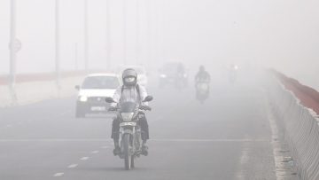 Motorists drive surrounded by smog in New Delhi.