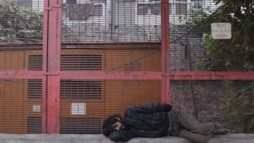 A homeless man sleeps out in the open next to a generator in Delhi's Kashmere Gate.