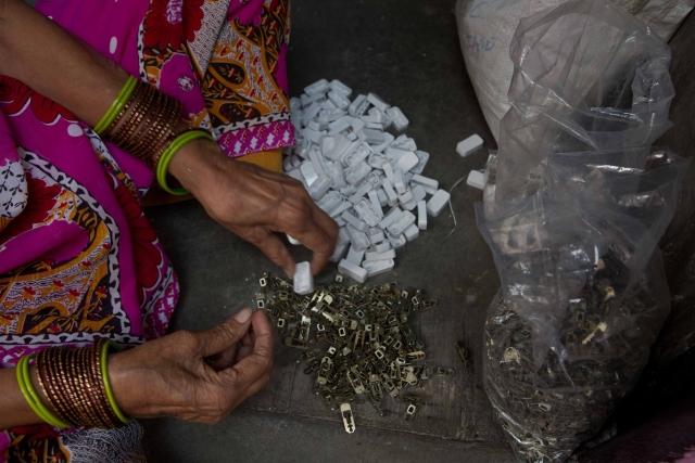 Nathu Devi putting together plastic switch covers inside her home in Kabir Nagar, north Delhi.