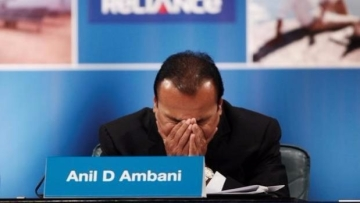 Chairman of debt-riddled Reliance Communications, Anil D Ambani hangs his head at a press conference.