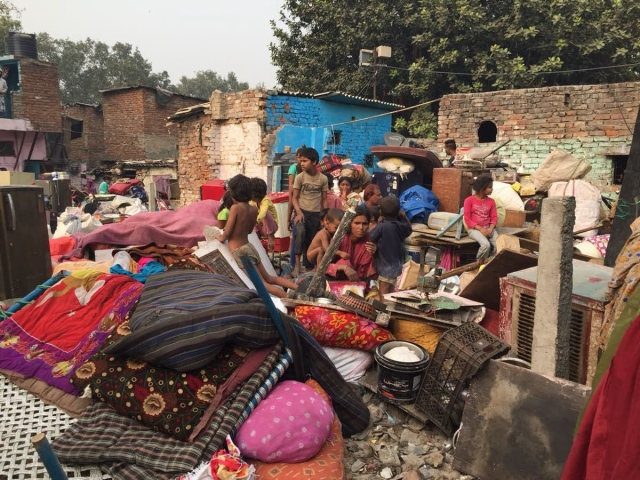 Settlers of Kathputli colony sit beside their belongings after their houses were demolished on 30 October.