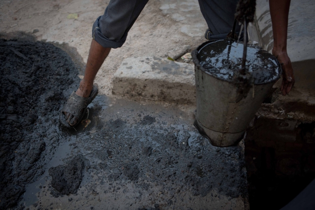 A worker empties a bucket of silt outside a drain in Sector 10, Ghaziabad.