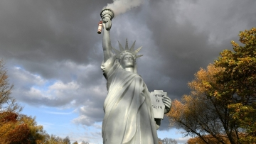 A replica of the Statue of Liberty  emits smoke in a park outside the 23rd UN Conference of the Parties  climate talks in Bonn, Germany, 17 November, 2017.