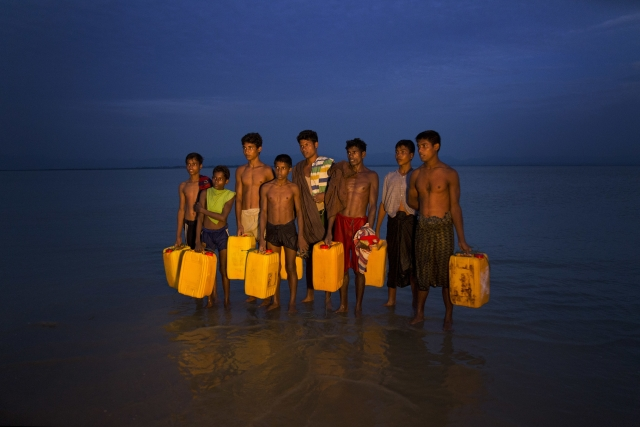 Newly arrived Rohingya Muslims carry yellow plastic drums they used as flotation aids and listen to Bangladeshi authorities