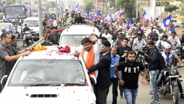 Patidar Anamat Andolan Samiti (PAAS) leader Hardik Patel waves at supporters during a roadshow for the second phase of Gujarat elections in Ahmedabad.