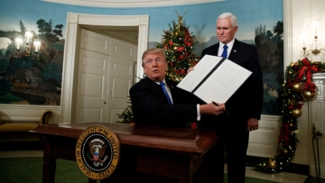 President Donald Trump, accompanied by Vice President Mike Pence, holds up a signed proclamation recognising Jerusalem as the capital of Israel in the Diplomatic Reception Room of the White House on 6 December.