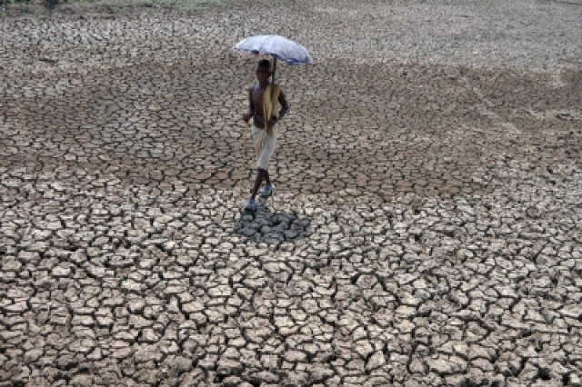 Bhubaneswar: A man walks through a dried pond on the outskirt of Bhubaneswar. The capital city of Odisha recorded 45 Degree Celsius. (Photo: IANS)