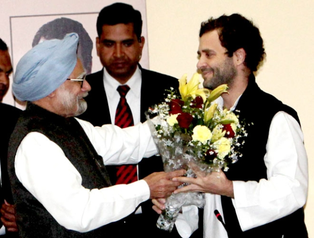 Former Prime Minister Manmohan Singh hands a bouquet to Rahul Gandhi, on his appointment as the vice president of the Indian National Congress.