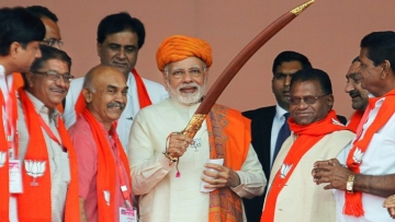 Prime Minister Narendra Modi being presented a sword by  supporters during an election campaign rally, at Dhandhuka village of Ahmedabad district on Wednesday, 6 December.