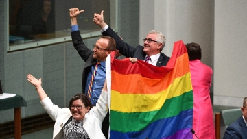 Members of Australian parliament celebrate the passing of the Marriage Amendment Bill in the House of Representatives at Parliament House.