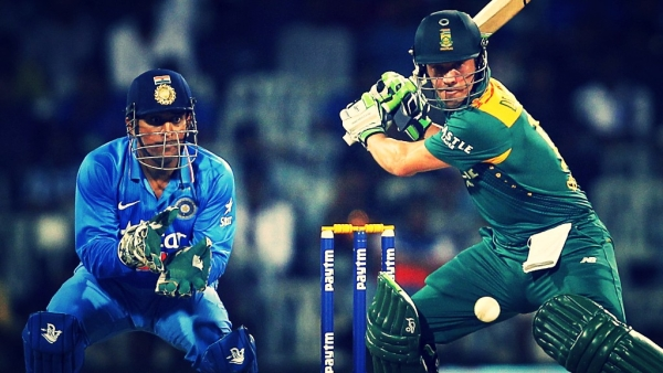 AB de Villiers plays a shot during an ODI as MS Dhoni looks on.