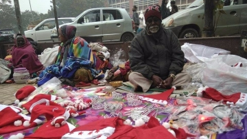 A homeless man hawks Christmas-themed goods on the sidewalk at Nehru Place, Delhi.