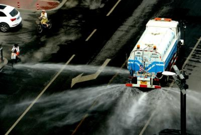 ZHENGZHOU, July 13, 2015 (Xinhua) -- A water cart sprays water on a street in Zhengzhou, capital of central China
