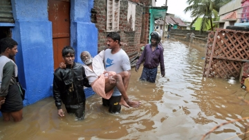 An elderly person is carried to a safe spot in a flooded locality following  heavy rains at Nagercoil in Kanyakumari district.