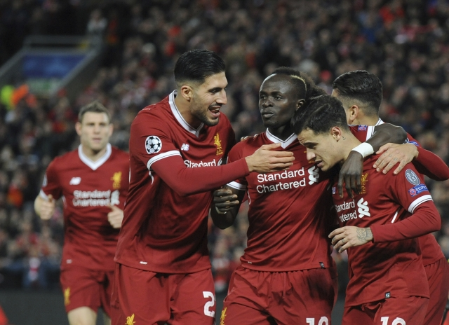 Liverpool's Philippe Coutinho, right, celebrates with his teammates after scoring his side's fifth goal.