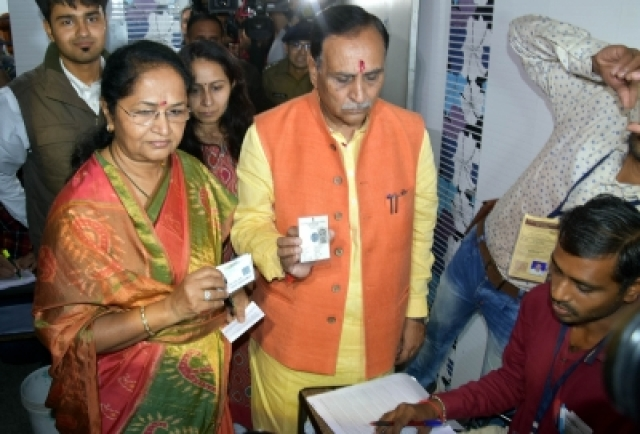 Rajkot: Gujarat Chief Minister Vijay Rupani and his wife Anjali Rupani at a polling booth during the first phase of Gujarat election in Rajkot on Dec 9, 2017. (Photo: IANS)
