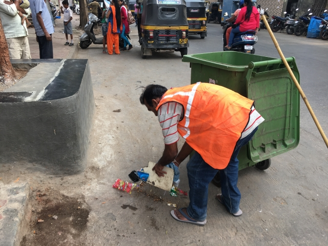 A BMC worker picks up garbage along the road without his gloves.
