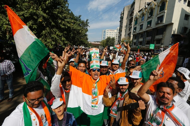 Supporters of the Congress celebrate outside a counting centre in Ahmedabad on 18 December.