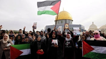 Palestinian women chant slogans and hold flags during a demonstration near the Dome of the Rock Mosque in the Al Aqsa Mosque compound in Jerusalem's old city.