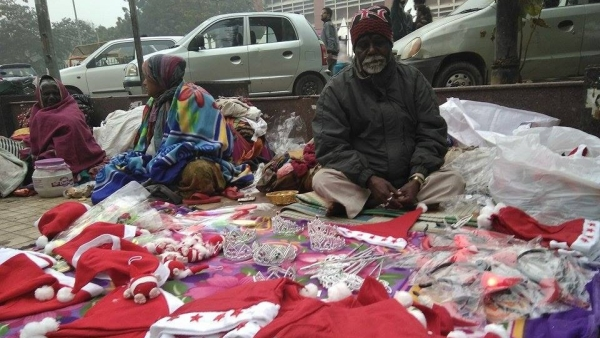 A homeless man hawks Christmas-themed goods on the sidewalk at Nehru Place, Delhi (<b>Photo: </b>Sunil Kumar Aledia)