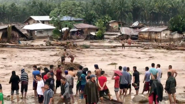 In this photo made from video by Aclimah Disumala on 22 December 2017, villagers carry cross raging flood waters in Lanao del Norte, Zamboanga Pennisula, southern Philippines.