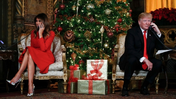 President Donald Trump and first lady Melania Trump speak on the phone with children as they track Santa Claus' movements with the North American Aerospace Defense Command (NORAD) Santa Tracker on Christmas Eve at the president's Mar-a-Lago estate in Palm Beach, Fla.