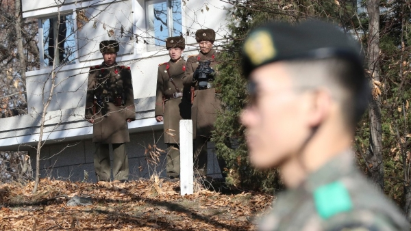 North Korean soldiers look at the South side as a South Korean stands guard near the spot where a North Korean soldier crossed the border on 13 November.