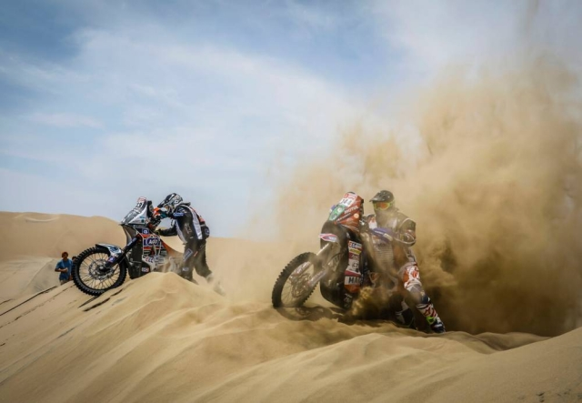 Two bike racers struggle to keep themselves balanced in the sand.
