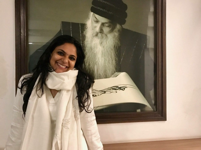 The author of this piece, Richa Anirudh, posing next to a picture of her guru, Osho Rajneesh.